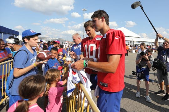 Daniel Jones and Eli Manning sign autographs for Giants fans after the first practice for the 2019 season. Thursday, July 25, 2019
