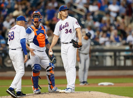 New York Mets' catcher Tomas Nido, center, and Mets' starting pitcher Noah Syndergaard (34), wait for Mets' pitching coach Phil Regan (58) to reach the mound during the third inning of a baseball game against the San Diego Padres, Wednesday, July 24, 2019, in New York. The Mets allowed three runs during the inning. (AP Photo/Kathy Willens)
