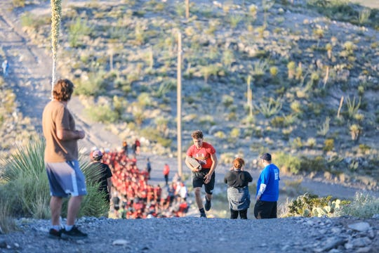 The Centennial high school football team hikes up A Mountain with rocks for the eighth year as part of their beginning of the season tradition in Las Cruces on Thursday, July 25, 2019.