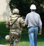 An Oakland County SWAT team members leads a DTE lineman to near the rear of a barricaded gunman's home in Novi on July 25 around noon.