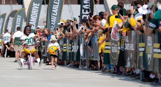 Green Bay Packers running back Jamaal Williams rides a young girl's bike outside Lambeau Field during the first day of training camp on July 25, 2019 in Green Bay, Wis.
