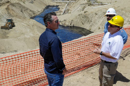 Gov. Gavin Newsom, left, is briefed by Billy Lacobie, of Chevron, center, and Cameron Campbell, of California department of conservation division of oil, gas, on Wednesday, July 24, 2019, while touring the Chevron oilfield in McKittrick, Calif. Newsom says he is encouraged by Chevron's efforts to clean up what has turned into the state's largest oil spill in decades. (Irfan Khan/Los Angeles Times via AP, Pool)