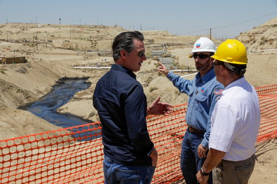 California Gov. Gavin Newsom, left, is briefed by Billy Lacobie, of Chevron, center, and Cameron Campbell, of California department of conservation division of oil, gas, on Wednesday, July 24, 2019 while touring the Chevron oilfield in McKittrick, Calif. Newsom says he is encouraged by Chevron's efforts to clean up what has turned into the state's largest oil spill in decades. (Irfan Khan/Los Angeles Times via AP, Pool)