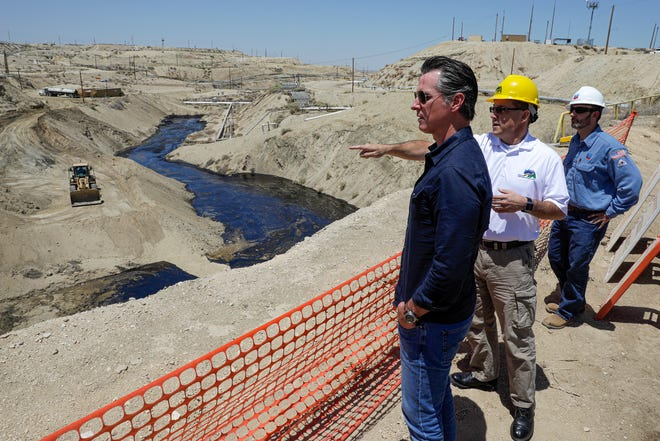 Gov. Gavin Newsom, left, is briefed by a staff member of the California state oil regulator, center, and Billy Lacobie, of Chevron, on Wednesday, July 24, 2019, while touring the Chevron oilfield in McKittrick, Calif. Newsom says he is encouraged by Chevron's efforts to clean up what has turned into the state's largest oil spill in decades. (Irfan Khan/Los Angeles Times via AP, Pool)