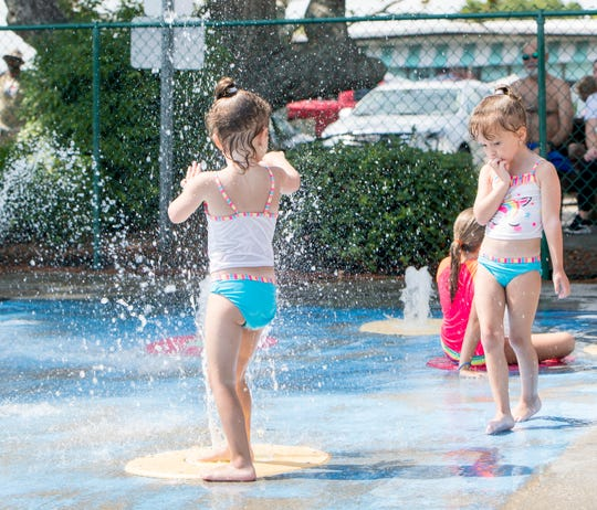 5-year-old twins Carabella, left, and Gabriella Peirano enjoy the splash pad at Navarre Park in Navarre on Thursday, July 25, 2019.at Navarre Park in Navarre on Thursday, July 25, 2019.