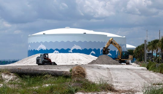 Several bulldozed piles of sand at the entrance to Pensacola Beach could remain in place for up to two years under an agreement between the Santa Rosa Island Authority and the Emerald Coast Utility Authority.