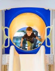 Rohan Coffey, 5, of Dayville, Connecticut, makes his way through a tunnel at Navarre Park on Thursday.