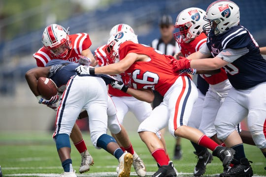 Jake Dickerson, center, helps tackle a ball carrier during a USA Football seventh grade bowl game at Tom Benson Hall of Fame Stadium in Canton, Ohio on June 29, 2019.