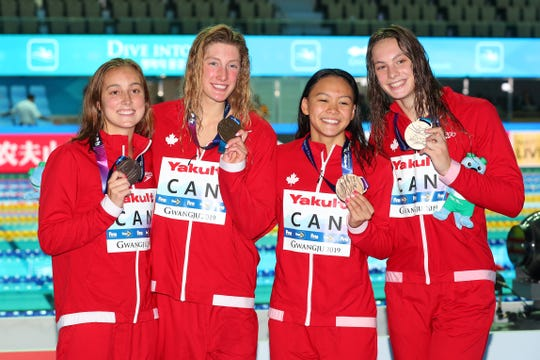 Taylor Ruck, left, of Scottsdale celebrates with her Canadian teammates after winning bronze medals in the 800 free relay at the World Swimming Championships.