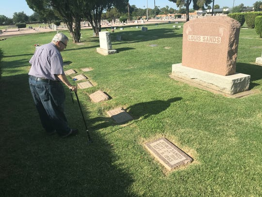 Ron Short looks at the graves of Louis Sands and his family.