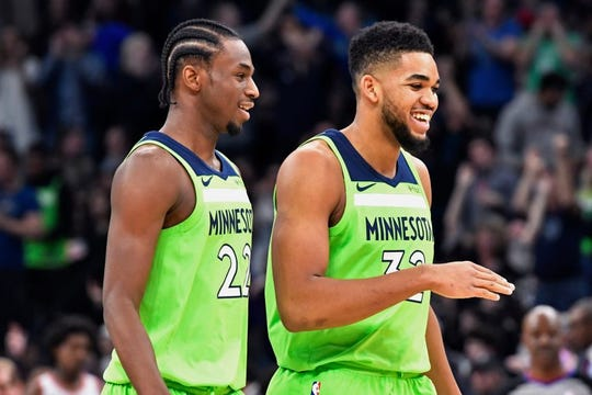 Minnesota Timberwolves' Andrew Wiggins, left, and Karl-Anthony Towns smile during the team's 115-109 win over the Toronto Raptors in an NBA basketball game Saturday, Jan. 20, 2018, in Minneapolis. (AP Photo/Jim Mone)