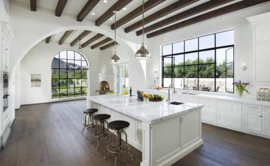 The $4.95M Paradise Valley mansion, sold by Joruca Holdings, LLC, features arched doorways, exposed wooden beams and steel framed windows.