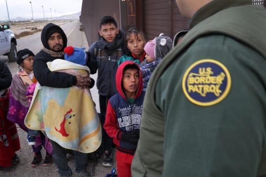 Un agente de la Patrulla Fronteriza conversa con una familia de migrantes.