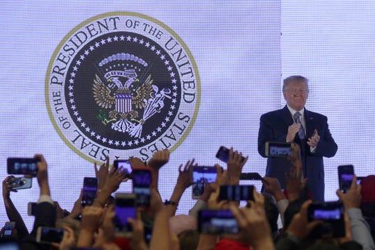 El presidente Donald Trump aplaude frente a un sello presidencial con un águila bicéfala y un juego de palos de golf cuando llega para dirigirse a la Cumbre de Acción de Estudiantes Adolescentes el 23 de julio de 2019 en Washington, DC.
