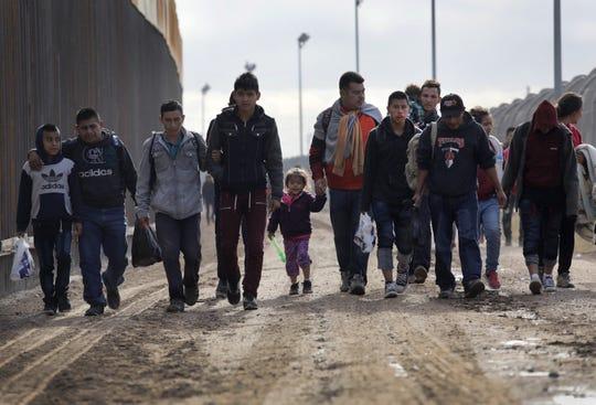 Migrantes centroamericanos caminan por un lado de la cerca que divide México y EEUU.