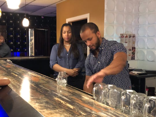 Mamajuana Lounge & Restaurant owner Gerelin Pena (left) and nightclub promoter Mr. Pena prepare drinks for thirsty diners.