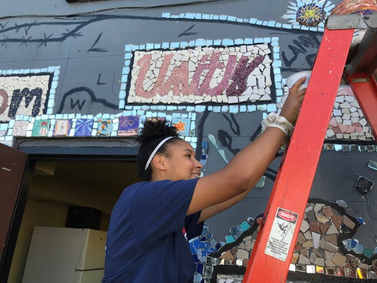 Nya Bantum, 13, makes her way up a ladder at Beautex Park while working on the mosaic on July 25.