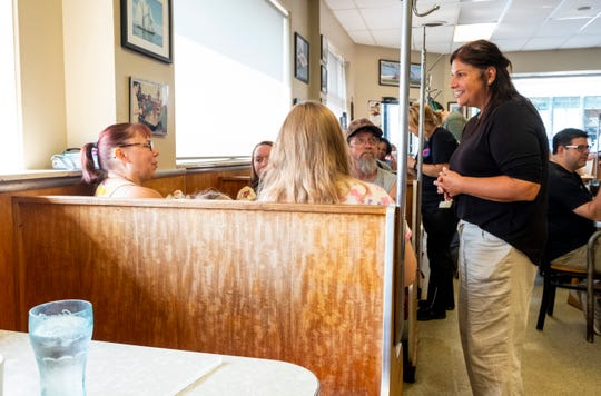 Mara McCalmon, right, one of the new owners of Cavis Grill, talks with a table Thursday, July 25, 2019, in the dining room of the restaurant on Quay Street in Port Huron.