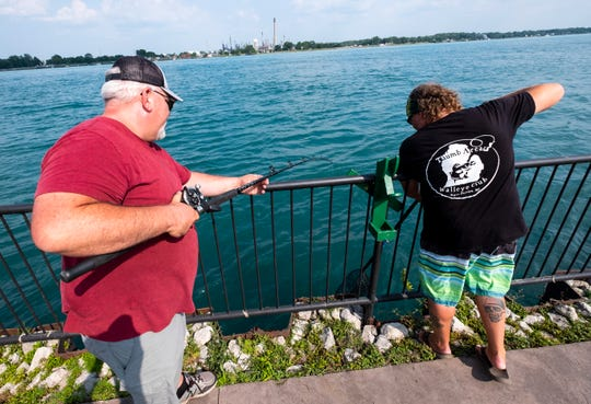Thumb Area Walleye Club President Robert MacLeod, left, and James Lottner, chairman of the club's board, work to reel in a line Thursday, July 25, 2019, during one of the club's contests near Chrysler Beach in Marysville.