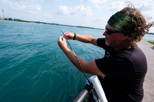 James Lottner, chairman of the board of the Thumb Area Walleye Club, loads bait onto a line hanging over the St. Clair River Thursday, July 25, 2019, near Chrysler Beach in Marysville.