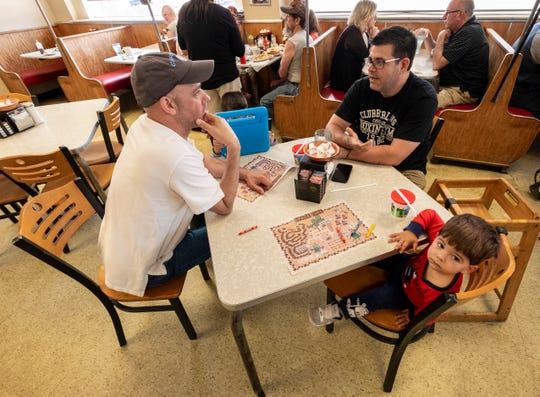 Chris Smith, left, sits at a table with Nick Cavis and his sons Theo, 2, and George 3, Thursday, July 25, 2019, at Cavis Grill in Port Huron. Nick Cavis who formerly owned the diner, recently sold it to Smith.