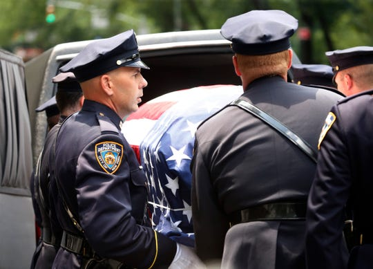 The NYPD honor guard places the casket of Robert Morgenthau into a herse waiting outside Temple Emanu-El on July 25, 2019.