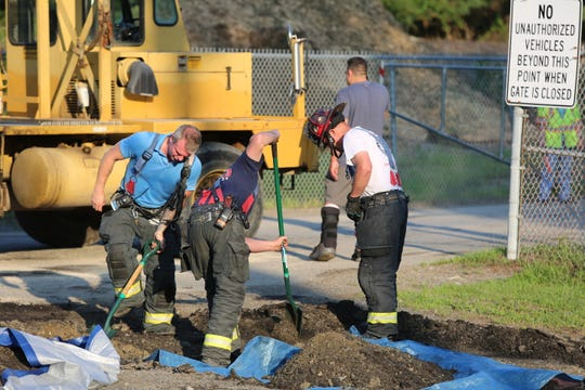 Firefighters work to dig up dirt that had been contaminated with oil on Thursday in East Fishkill.