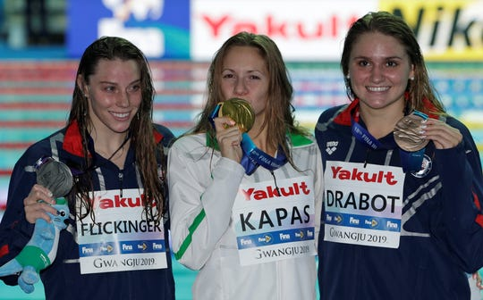 Spring Grove High School graduate Hali Flickinger, left, holds her silver medal after finishing second in the 200-meter butterfly at the World Swimming Championships in Gwangju, South Korea, on Thursday, July 25, 2019. Hungary's Boglarka Kapas, center, kisses her gold medal. Bronze medalist Katie Drabot is at right. (AP Photo/Mark Schiefelbein)