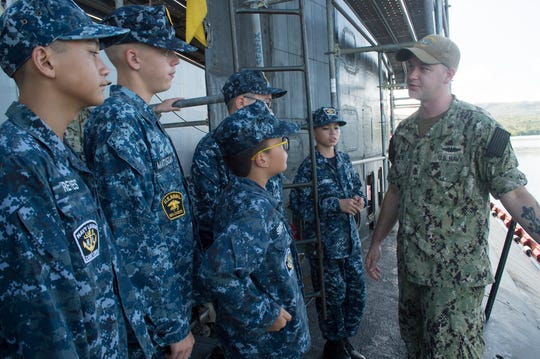 Chief Machinist's Mate (Auxiliary) Jeramiah Andrew, a native of Cambridge City, Indiana, speaks to members of the U.S. Navy Sea Cadet Pacific Guam Program during a tour of USS Asheville.