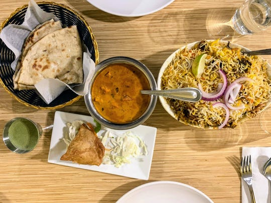Butter naans, samosa with chutney, chicken tikka masala and chicken biryani are among the dishes at Hyderabad House of Biryani.