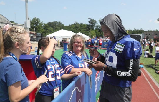Levi Wallace stops to sign autographs for fans during training camp.