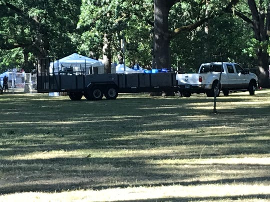 Vehicles drove and parked on tree roots in Bush's Pasture Park during the 2019 Salem Art Fair and Festival