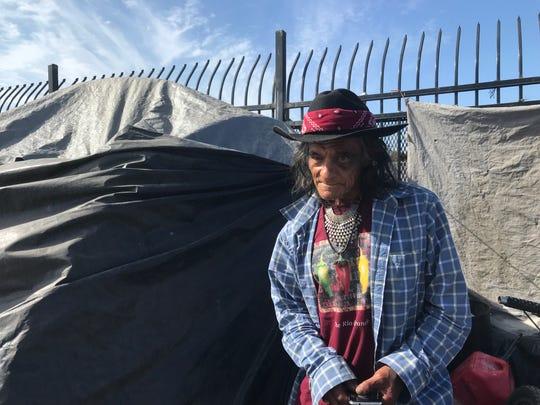 Adrián Morfin de pie frente a su tienda de campaña, mostrando su ojo morado. Dice que fue golpeado por otro indigente. 25 de junio de 2019.