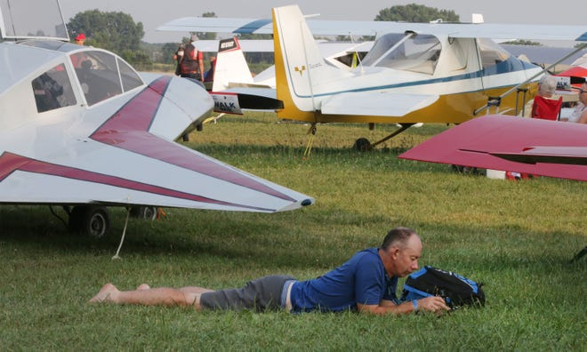 Paul Anderson of New Zealand looks over his cellphone during a break in action at the Experimental Aircraft Association's Airventure convention, Wednesday, July 24, 2019, in Oshkosh, Wis.