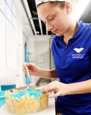 Kayla Leyden, the senior aquarist at Shreveport Aquarium, makes a cake for their shark, Zenon.