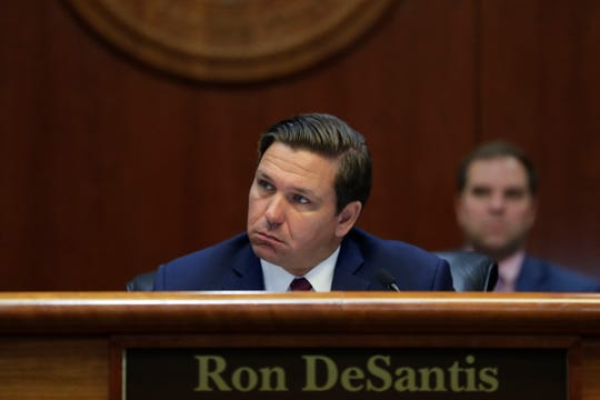 Gov. Ron DeSantis listens as attorney Michael Tein, representing former Office of Financial Regulation Commissioner Ronald Rubin, speaks during a Florida Cabinet meeting Thursday, July 25, 2019.