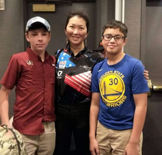 "Peyton Green (left) of Tallahassee and Christopher Jones of Climax, Georgia caught up with pool icon Jeanette ""Black Widow"" Lee at the American Poolplayers Association Junior Championships in St. Louis."