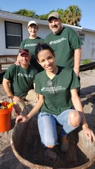 CDL's Yinett Florentino, foreground, has fun in the wheel barrel with Rick Gray, left, Nancy Gray and Martin Woods during a Habitat for Humanity of Martin County home build in April.