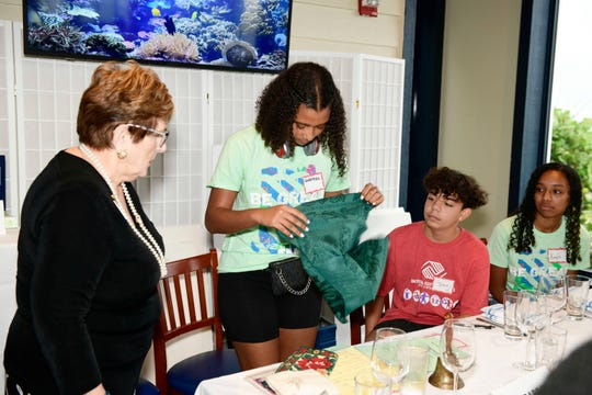 Barbara Benson Wymer, left, shows Boys & Girls Club members Gabriella, Jose V. and Kayla W. the art of napkin folding at a recent life skills seminar at Kyle G's Prime Seafood and Steaks.