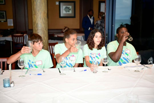St. Lucie County Boys & Girls Club members Dominick S., left, Elyse B., Megan and Jedd learn how to give a toast at a seminar on business and life skills at Kyle G's Prime Seafood and Steaks.