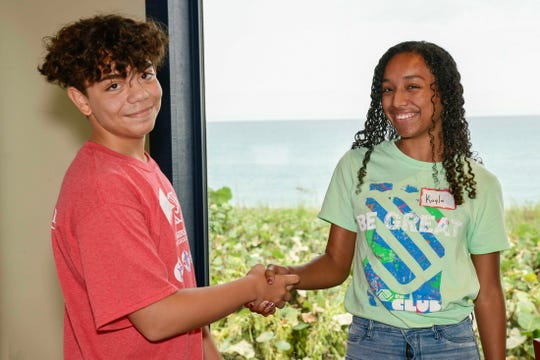 St. Lucie County Boys & Girls Club members Jose and Kayla learn to shake hands at a recent program on business and life skills at Kyle G's Prime Seafood and Steaks.