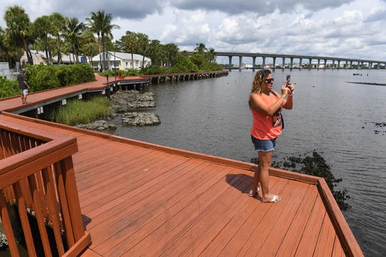 "Kathy Wickham (left) records a video panoramic of the St. Lucie River on her cellphone while walking the Stuart Riverwalk with her friend Bruce Williams (background) after lunch on Thursday, July 25, 2019, in downtown Stuart. ""I enjoy it a lot, it's gorgeous,"" Wickham said about the downtown Riverwalk. ""I think that it's something that we need, it's part of our lifestyle, the scenery, it's what brings people here."" The City of Stuart is beginning to replace the Riverwalk decking around City Hall and Flagler Park."
