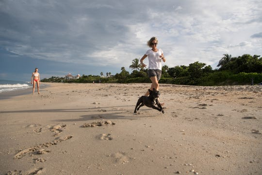 "Valeria Baluk, who lives in Weston and is vacationing in Indian River Shores, runs with the family's French bulldog, Napoleon, on the beach Wednesday, July 24, 2019, off Beachcomber Lane. ""We've been coming for the last three years, always the same house,"" Baluk said. A big draw for the family is the dog friendliness of the beach. ""This is the only opportunity we have to bring them with the kids,"" she added, ""they really enjoy that."" Unleashed dogs are now allowed on Indian River Shores beaches daily from sunrise to 9 a.m. and from 5 p.m. to sunset, provided they have special tags issued by the Public Safety Department."