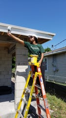 CDL's Anna Knox paints fascia boards during a Habitat for Humanity of Martin County home build in April.