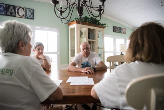 "Richard Sullivan (center) and wife Kathey (far left) host neighbors and fellow members of The Sierra Club, Elaine Lavallee (right) and June Downs, at their home July 16, 2019, in the Indianwood Golf & Country Club in Indiantown. They meet to address sugar cane field burning. ""We enjoy the people, we enjoy the climate; unfortunately, we've been subjected to the air pollution,"" Richard Sullivan said. ""If we're in the wrong end of which way the wind is blowing, we're subjected to the smoke from the burning ... and also the ash that gets all over everything."""