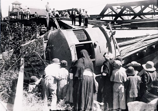 July 29, 1910 A n El Paso-Juarez sreetcar rest ignobly on its side in the muddy bed of the Rio Grande after the Santa Fe Street Bridge collapsed under its weight.