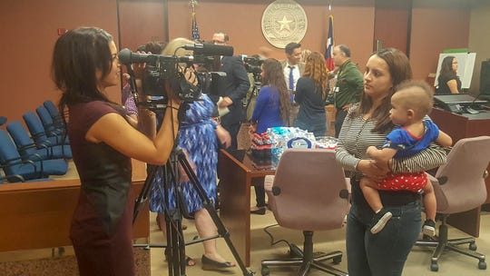 "Taylor Alaniz, an ""aged-out"" foster youth interviews while holding her daughter Aaliyah in 2016. She was honored at the El Paso County Court for her completion of Project FUTURE, a six-week internship with El Paso County."