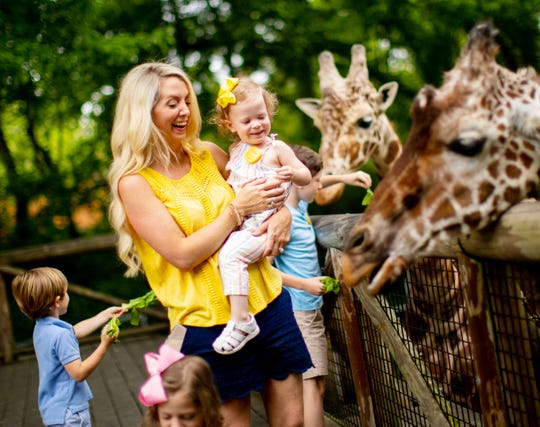 A young girl enjoys the giraffes at the Memphis Zoo while wearing a Laugh Tracker.