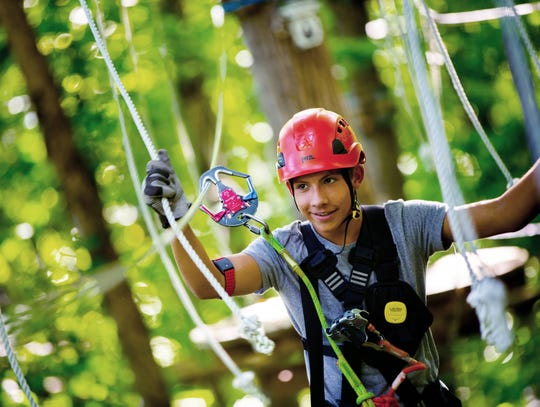 A boy wears a Laugh Tracker on a zip line course at Navitat in Knoxville.