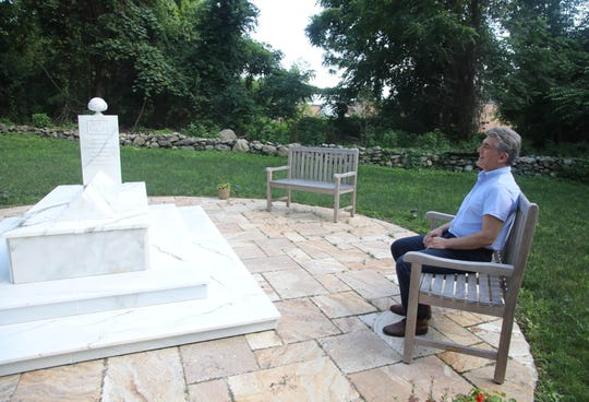 Sheikh Yurdaer Doganata at Jerrahiof America mosque stands near the burial plot of the late imam Tosun Bayrak in Chestnut Ridge on July 24, 2019. The village is working on a law to prohibit backyard burials.